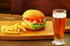 Delicious hamburger with beef, onion, tomato, lettuce and cheese with french fries and a glass of beer on wooden board.  Royalty Free Stock Image