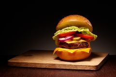 Hamburger with cheese, pickles, tomato, onions, lettuce on board Royalty Free Stock Photos