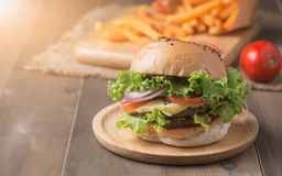 Delicious hamburger and french fries on wooden background Stock Photography