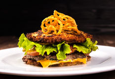 Delicious hamburger potato pancakes bun. latke burger with lettuce, cheese, tomatoes on wooden black background and Royalty Free Stock Images