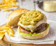 Hamburger served with a topping of guacamole and homemade french fries stock images