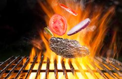 Delicious hamburger steak on cast-iron grate. With fire flames stock images