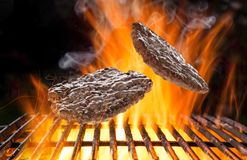 Delicious hamburger steak on cast-iron grate. With fire flames Royalty Free Stock Images