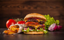 Delicious hamburger on wood. Delicious hamburger served on wooden planks stock photos