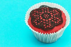 Delicious handmade red cupcake on blue background. Royalty Free Stock Image