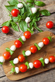 Delicious healthy antipasti snack caprese, skewers. With mozzarella basil and tomatoes. Healthy organic vegetarian food on wooden table background. Rustic style Stock Photo