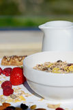 A delicious and healthy breakfast in the garden of muesli with milk, nuts Stock Image