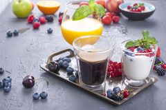Delicious and healthy breakfast, gray background and napkin. Yogurt, muesli, granola, raspberry and blueberry berries, fresh. Orange juice and fragrant morning royalty free stock image