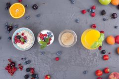 Delicious and healthy breakfast, gray background and napkin. Yogurt, muesli, granola, raspberry and blueberry berries, fresh. Orange juice and fragrant morning stock photography