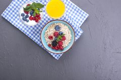 Delicious and healthy breakfast, gray background and napkin. Yogurt, muesli, granola, raspberry and blueberry berries and fresh. Orange juice. Copy space stock photo