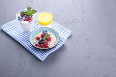 Delicious and healthy breakfast, gray background and napkin. Yogurt, muesli, granola, raspberry and blueberry berries and fresh. Orange juice. Copy space royalty free stock images