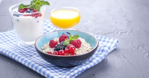 Delicious and healthy breakfast, gray background and napkin. Yogurt, muesli, granola, raspberry and blueberry berries and fresh. Orange juice. Copy space stock photography