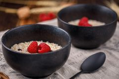 Delicious and healthy breakfast with oatmeal and fresh raspberries in delicious bowls. Close-up Royalty Free Stock Photos