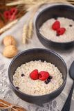 Delicious and healthy breakfast. Still life with oatmeal and fresh raspberries in refined bowls. Close-up Stock Photography