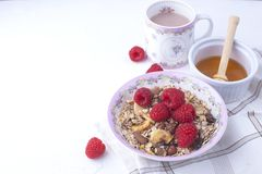 Delicious and healthy breakfast on a white background. Porridge of oatmeal, raspberry, honey, coffee for a good morning. Free stock photography