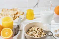 Delicious Healthy breakfast. Whole Grain Cereal rings, milk, honey and orange juice on the white table. Cheerios whole grain cere. Als with milk. Healthy stock image