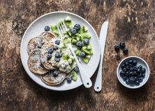 Delicious healthy breakfast - whole wheat pancakes with greek yogurt, blueberries, kiwi, honey and nuts on a wooden background, to stock photos