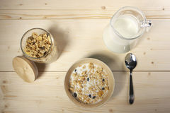Delicious and healthy cereal in bowl with milk on table Stock Photos