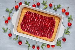Delicious healthy dessert - cherry pie in the baking dish on the gray kitchen table. Cold summer tart decorated with cherry jelly stock photos