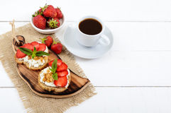 Delicious healthy dietary breakfast: rye bread with cottage cheese and strawberries and a cup of coffee espresso Royalty Free Stock Photography