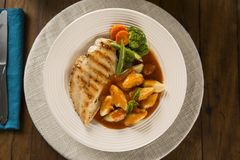 Delicious healthy food with grilled chicken, gnocchi potato, red sauce and vegetables on the plate. View from the top.  stock photos