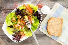 Delicious healthy fresh salad and brussels sprouts. Delicious fresh leafy green mixed salad with diced and sauteed brussels sprouts served on a rustic wooden Royalty Free Stock Images