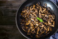 Delicious and healthy fried Mushroom champignon with olive oil, onion, garli, chilli and basil on rustic table.  royalty free stock image