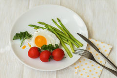 Delicious healthy gourmet breakfast it`s traditional homemade fried eggs and fresh asparagus served with tomatos on the Stock Image