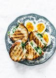 Delicious healthy nutritious breakfast - hot spinach and mozzarella sandwiches and boiled eggs. On a light background Stock Photo