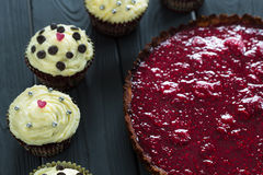Delicious Healthy Raw Raspberry Tart with Valentines Day Red Velvet Cupcakes on Dark Wooden Background Royalty Free Stock Images