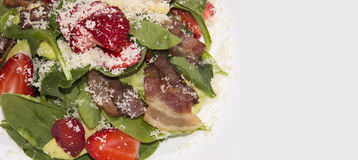 Delicious and healthy salad with arugula, strawberry, cheese and bacon. background royalty free stock photos