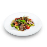 Delicious healthy warm salad with beef and vegetables. On a round plate isolated on white stock image