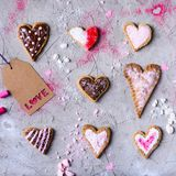 Delicious heart shaped cookies with love tag on grey cracked surface. Top view of delicious heart shaped cookies with love tag on grey cracked surface Royalty Free Stock Image