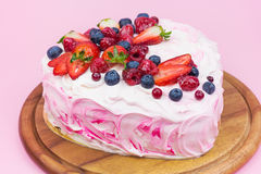 Delicious heart shaped cream cake with berries. Sweet heart cake decorated with fresh fruits on pink background Royalty Free Stock Photo