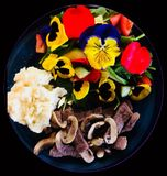 Delicious home cooked potato beef and fresh garden salad with flower petals and natures greens. Delicious home cooked potato beef and fresh garden salad with Stock Images