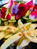 Delicious home cooked potato fries fresh garden salad with flower petals and natures greens. Delicious home cooked potato fries fresh garden salad with flower Royalty Free Stock Image