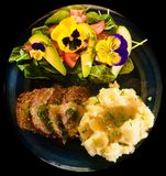 Delicious home cooked potato meat fresh garden salad with flower petals and natures greens. Delicious home cooked potato meat fresh garden salad with flower Stock Photography