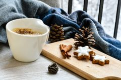 Winter weekend. Delicious home made  cinnamon   star cookies ,cup of coffee  sarf  in a  balcony in snowy day. Lazy winter weekend with a book on the sofa Stock Photo