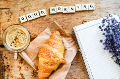 Breakfast. Delicious home made croissant,coffee ,notebook  and   fresh lavender  on wooden background. and good morning  written from scruble letters Stock Images
