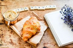 Breakfast. Delicious home made croissant,coffee ,notebook  and   fresh lavender  on wooden background. and good morning  written from scruble letters Royalty Free Stock Image