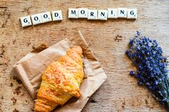 Breakfast. Delicious home made croissant,coffee ,notebook  and   fresh lavender  on wooden background. and good morning  written from scruble letters Royalty Free Stock Images