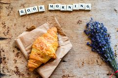 Breakfast. Delicious home made croissant  fresh lavender  on wooden background. and good morning  written from scruble letters Royalty Free Stock Images