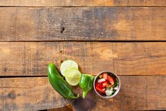 A delicious home made salsa pico de gallo with tomato, onion, li. Me, cilantro, and jalapeno pepper served on rustic wooden table. Selective Focus With Copy stock images