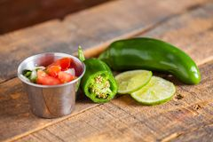 A delicious home made salsa pico de gallo with tomato, onion, li. Me, cilantro, and jalapeno pepper served on rustic wooden table. Selective Focus royalty free stock image