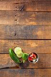 A delicious home made salsa pico de gallo with tomato, onion, li. Me, cilantro, and jalapeno pepper served on rustic wooden table. Selective Focus With Copy stock photo
