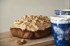 Delicious home-made walnut and coffee cake with hot beverage cups aside. Table with wooden board where it rests a delicious cake with coffee icing and chopped Stock Photo
