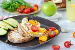 A delicious home style breakfast with eggs, toasted bread, , green apple,colorfull tomatoes, parsley and mint, lemonade, stock photos