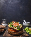 Delicious homemade burger with chicken in mustard sauce with arugula and herbs on a cutting board lettuce and spices border , Stock Image