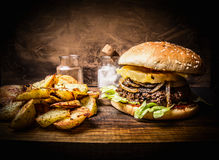 Delicious homemade burger with meat, onions, lettuce and pineapple, potato wedges on wooden rustic cutting board close up Stock Photos