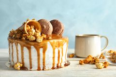 Delicious homemade cake with caramel sauce. And popcorn on table Royalty Free Stock Photos
